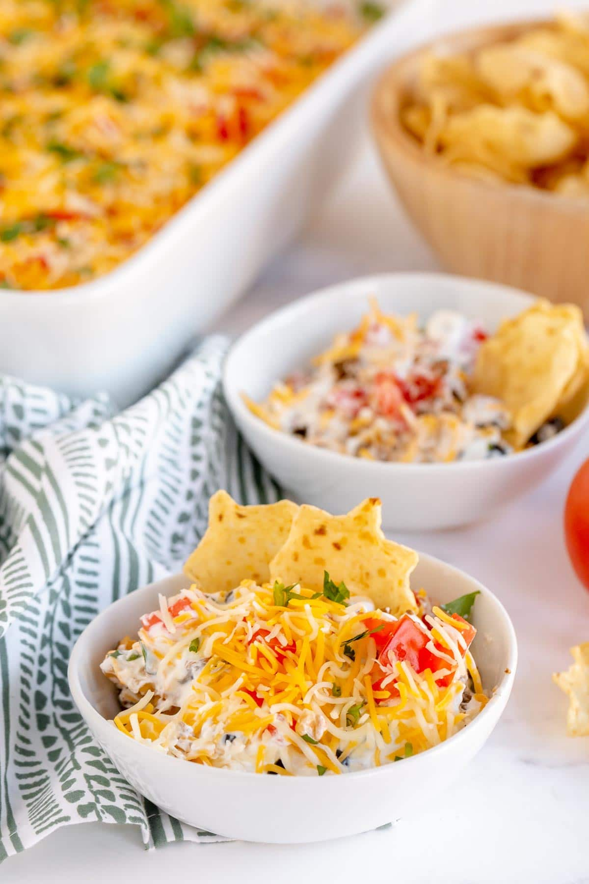 Two bowls of layered taco dip with chips