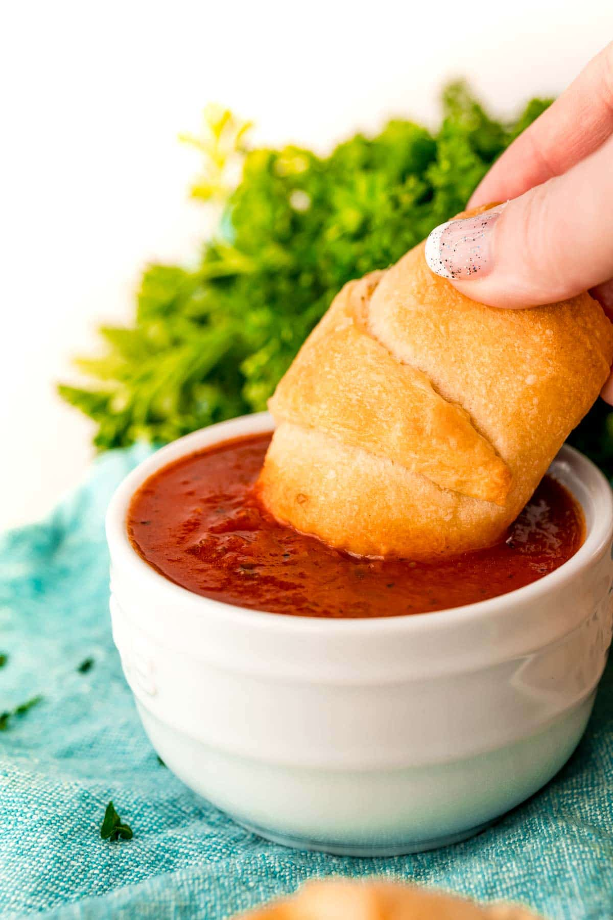 Pizza roll up being dipped in pizza sauce
