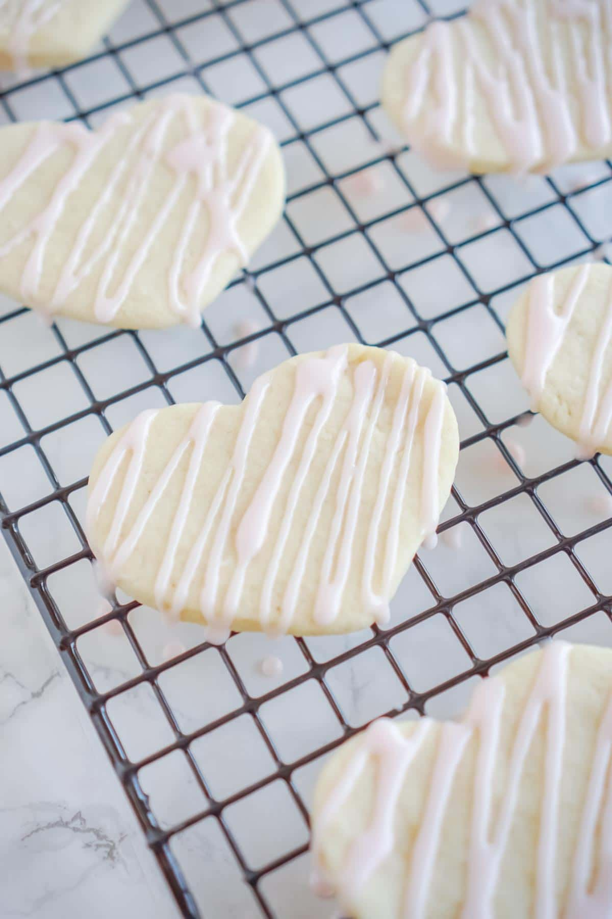 heart shaped cookies with sugar cookie icing on a baking rack