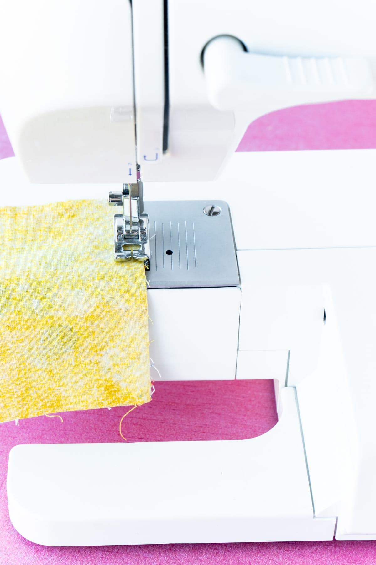 Sewing machine with two pieces of yellow fabric