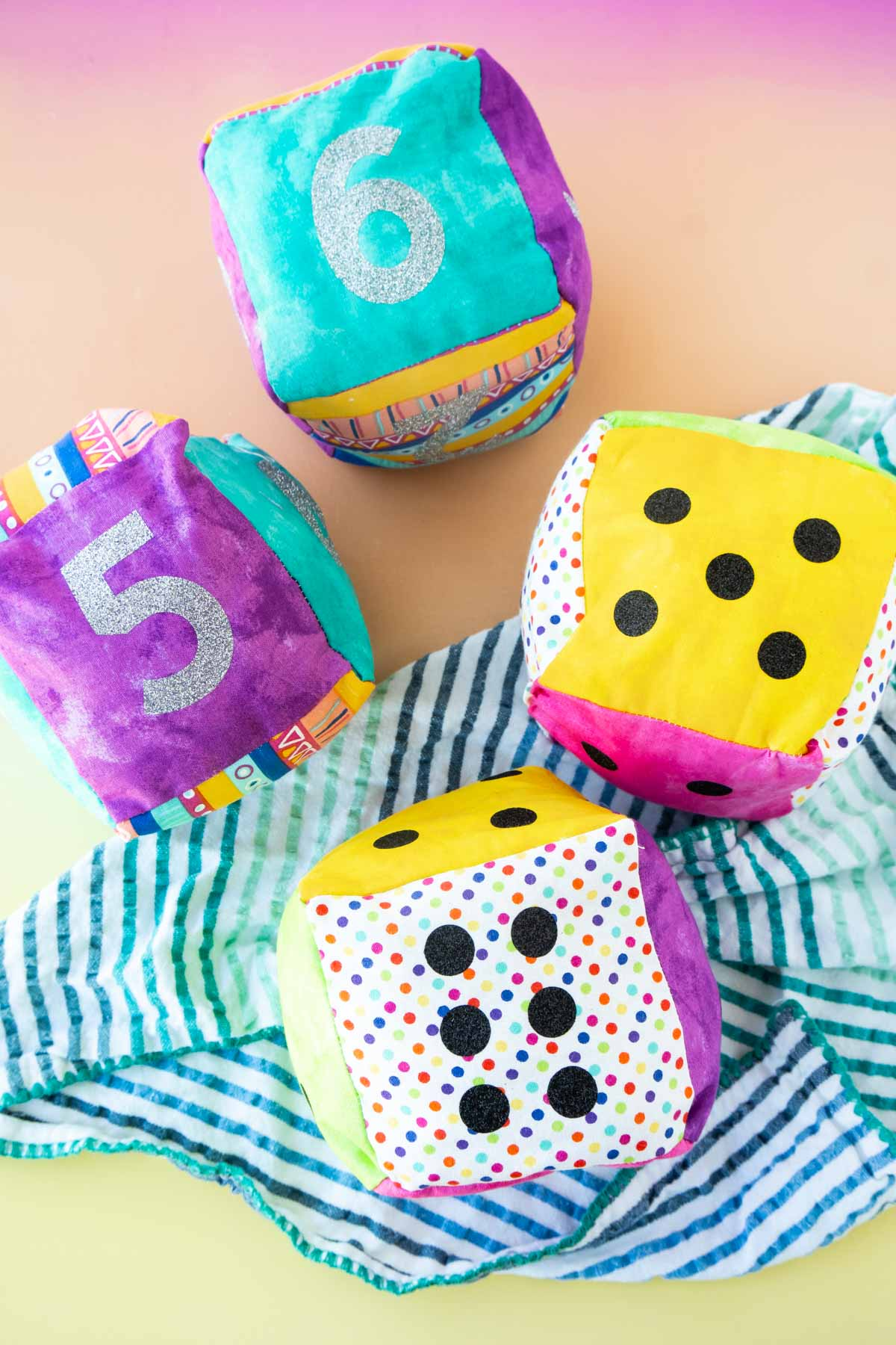 Two sets of fabric DIY dice on a colored background