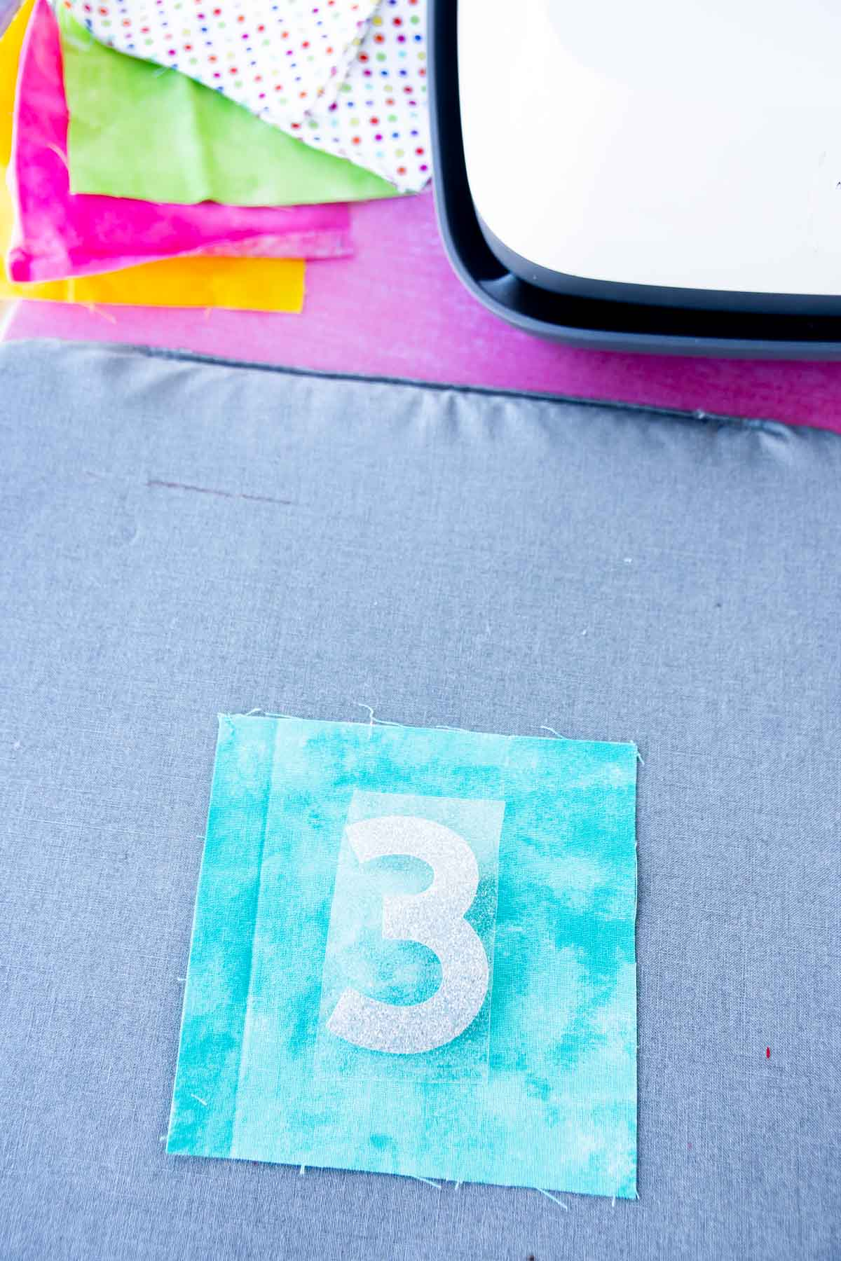 Fabric square with an iron on three on top of it