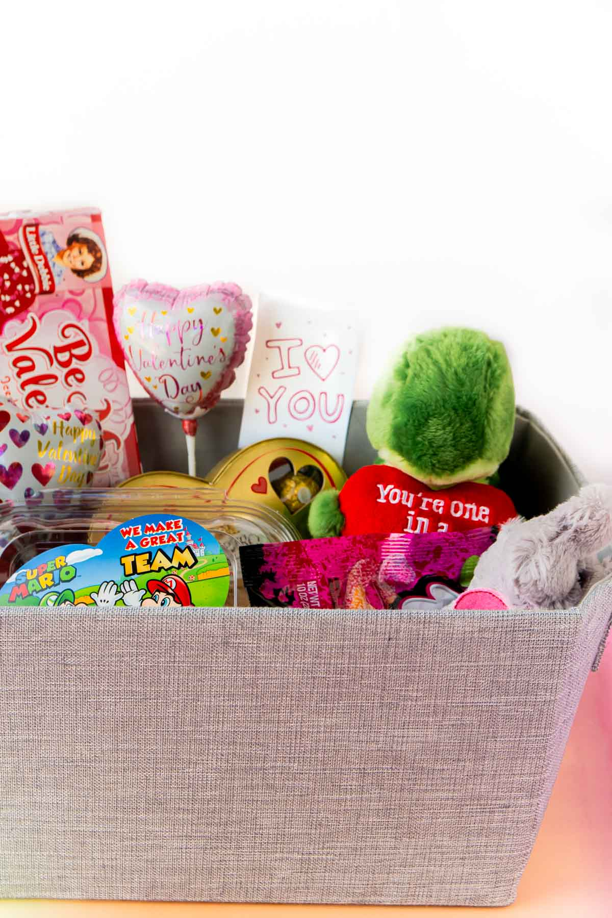 Gray gift basket with stuffed animals coming out