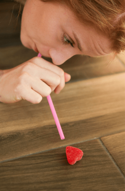 Girl blowing a heart with a straw