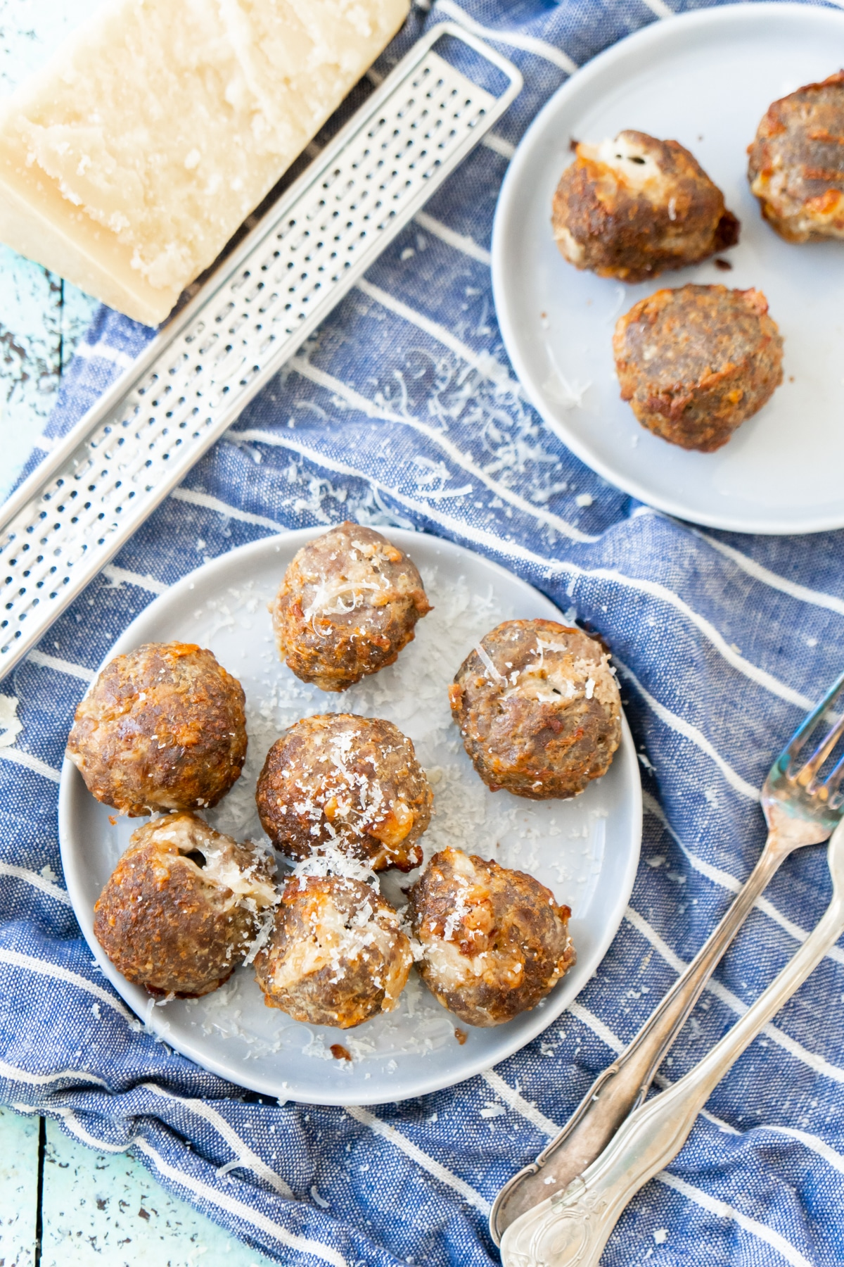 Two white plates with cheese stuffed meatballs
