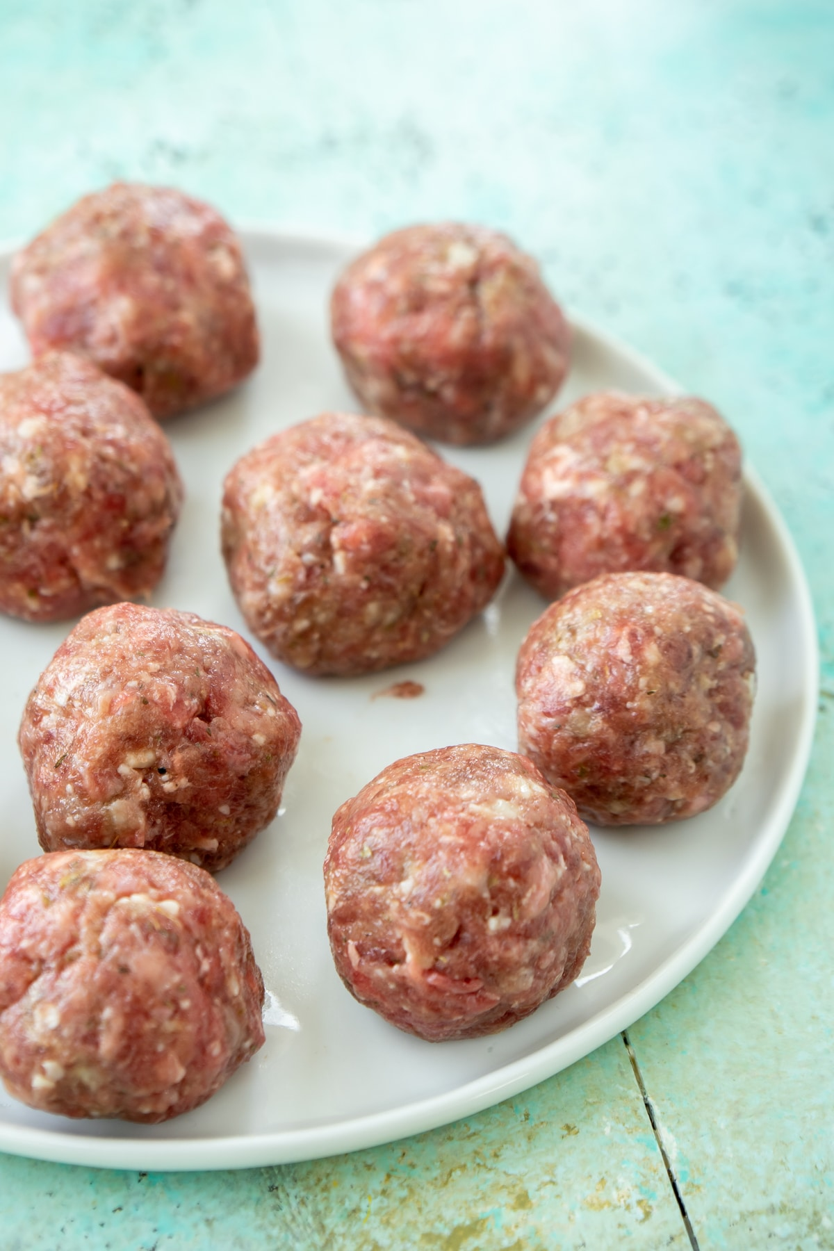 white plate with uncooked cheese stuffed meatballs