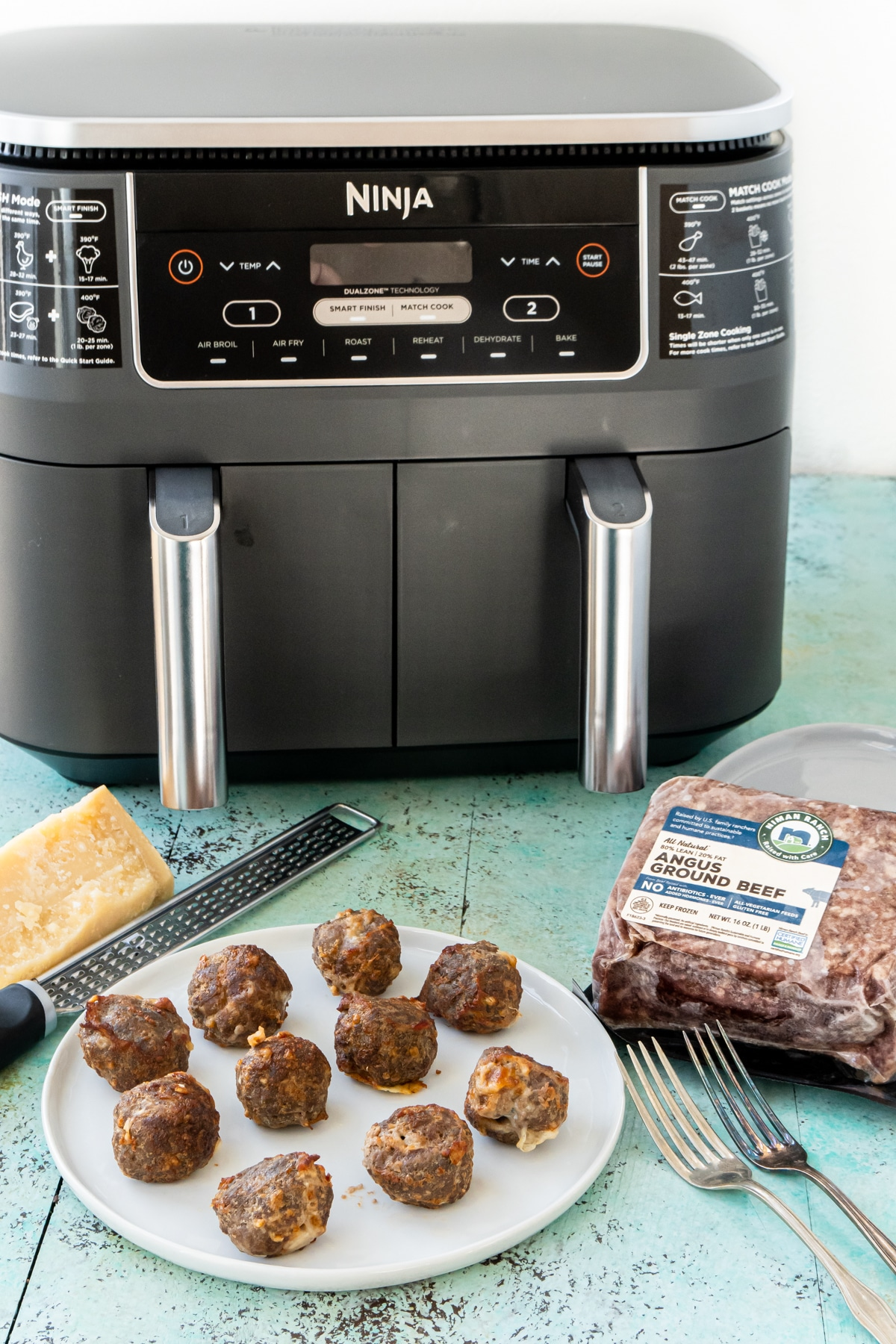 cooked cheese stuffed meatballs on a plate in front of an air fryer