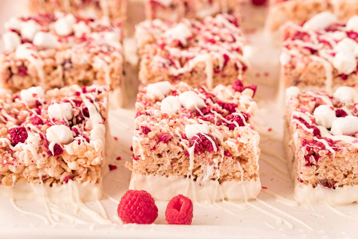 Row of white chocolate dipped rice krispie treats with a raspberry in front