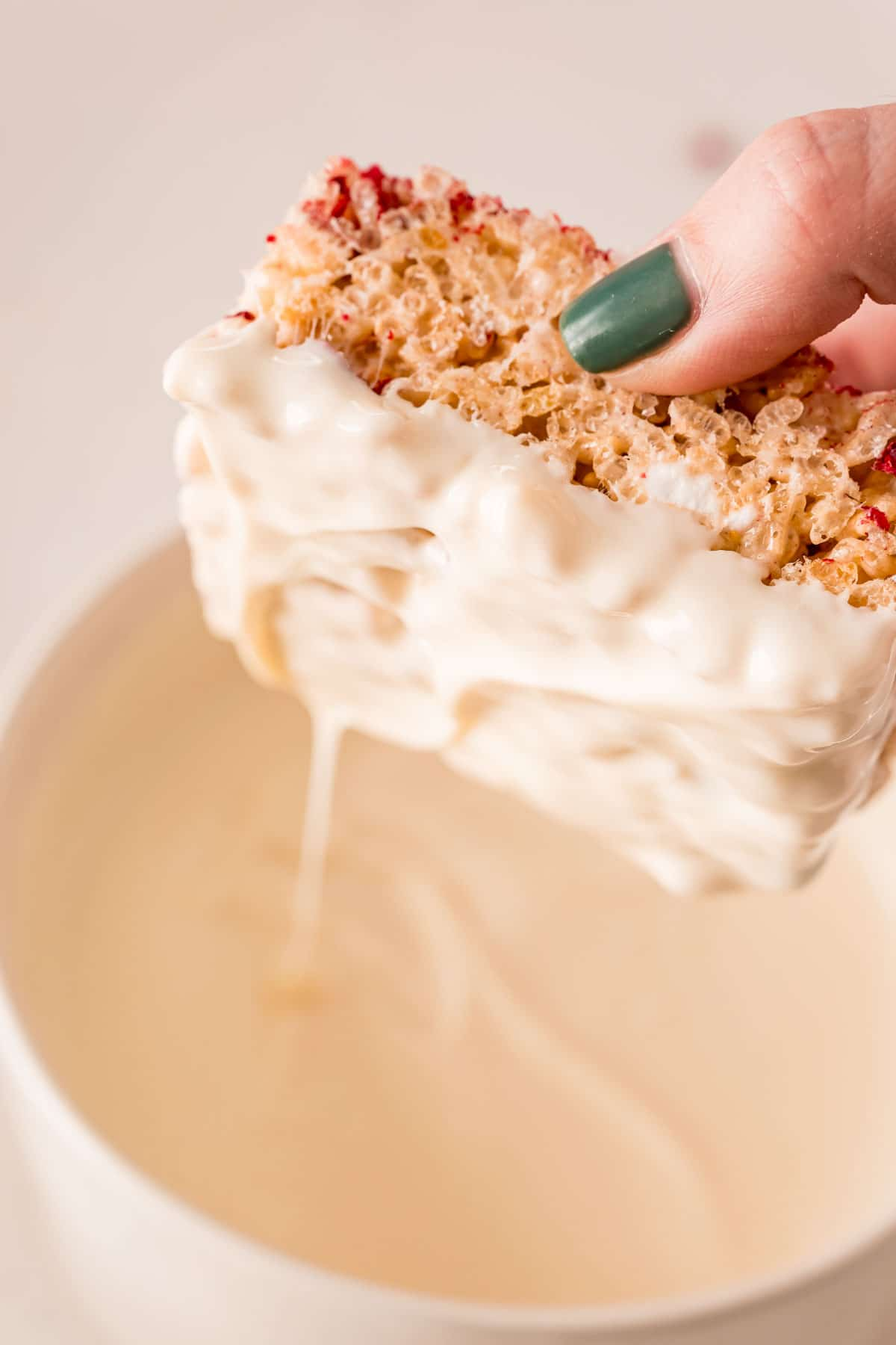 Rice krispie treat being dipped in white chocolate