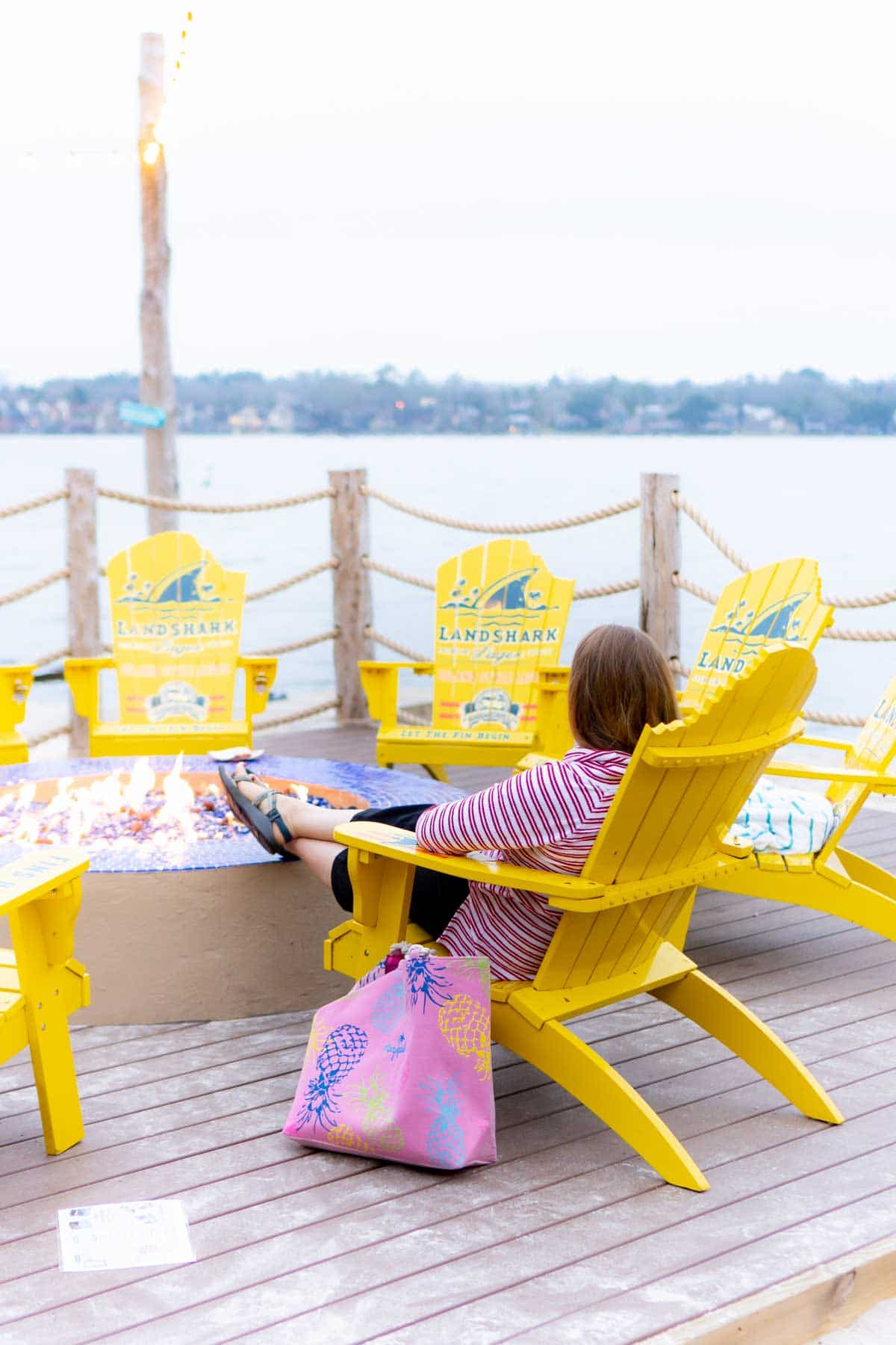 Woman sitting in a yellow chair next to Lake Conroe