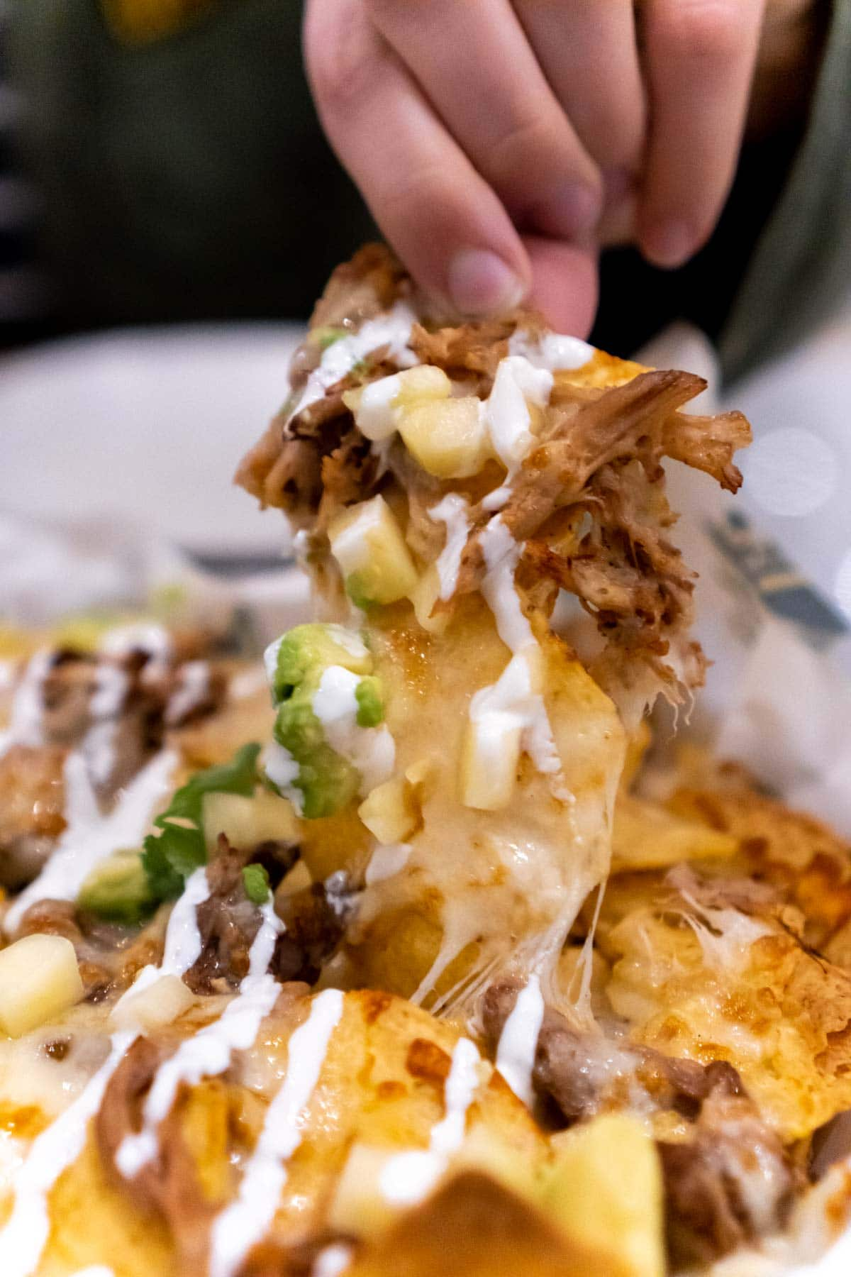 Woman's hand pulling a chip in carnitas nachos