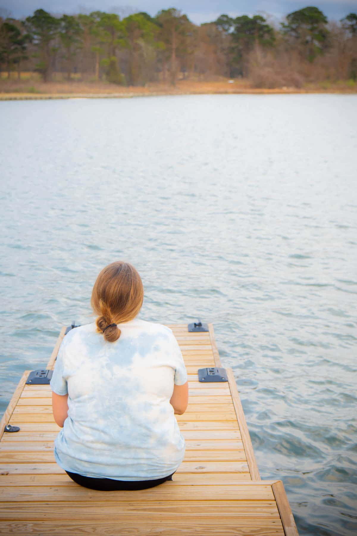 Woman sitting on a dock at Margaritaville Lake Conroe