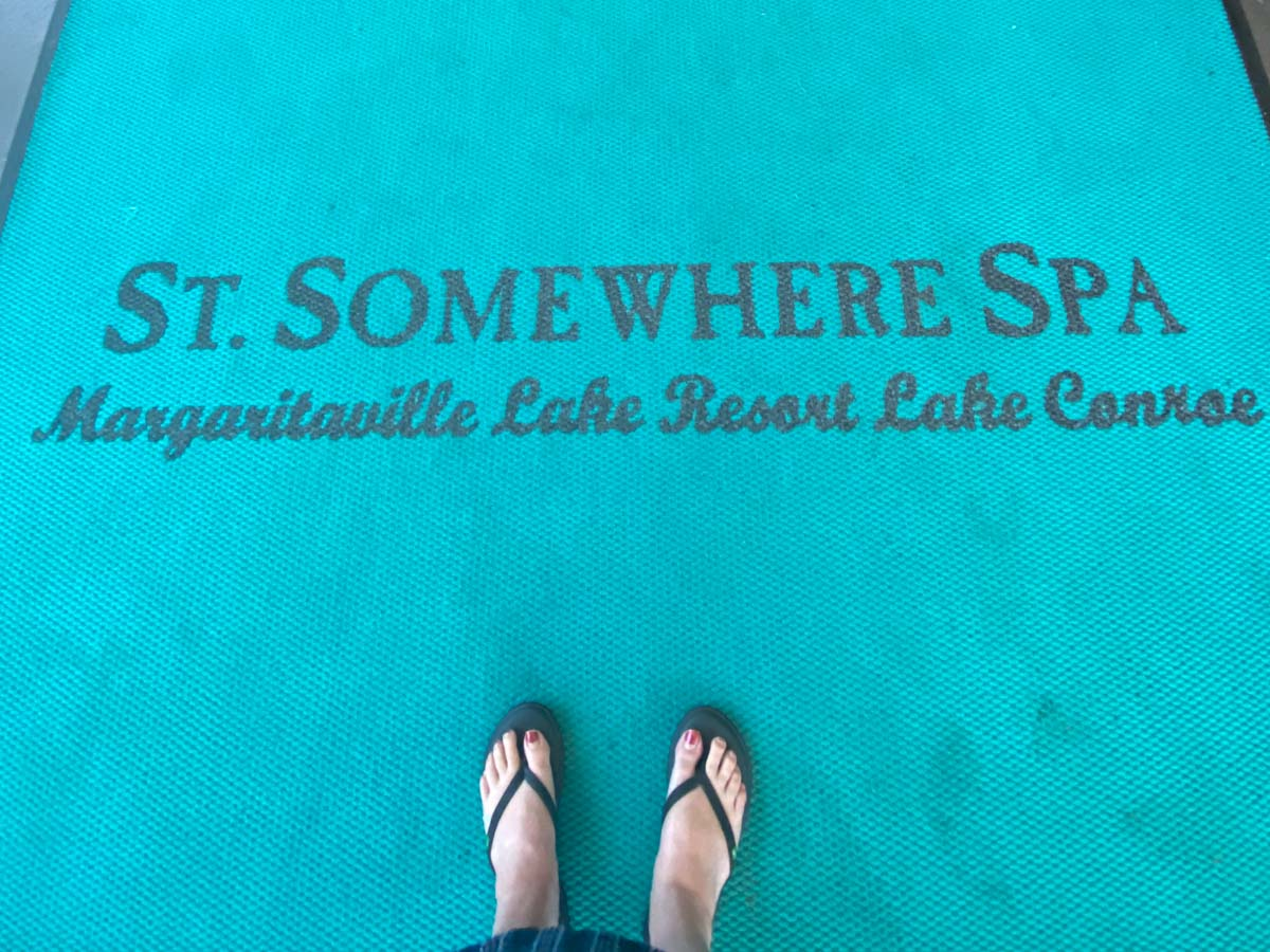 Womans' feet on a blue st somewhere spa entry mat