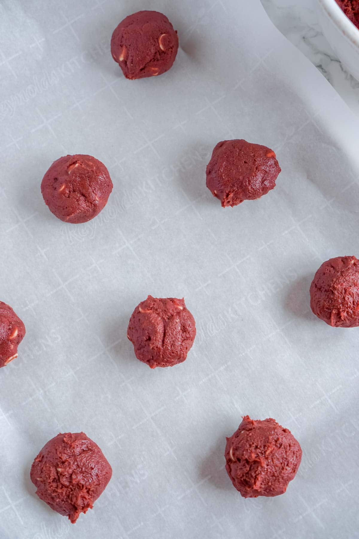 Red velvet cookie dough balls on a baking sheet