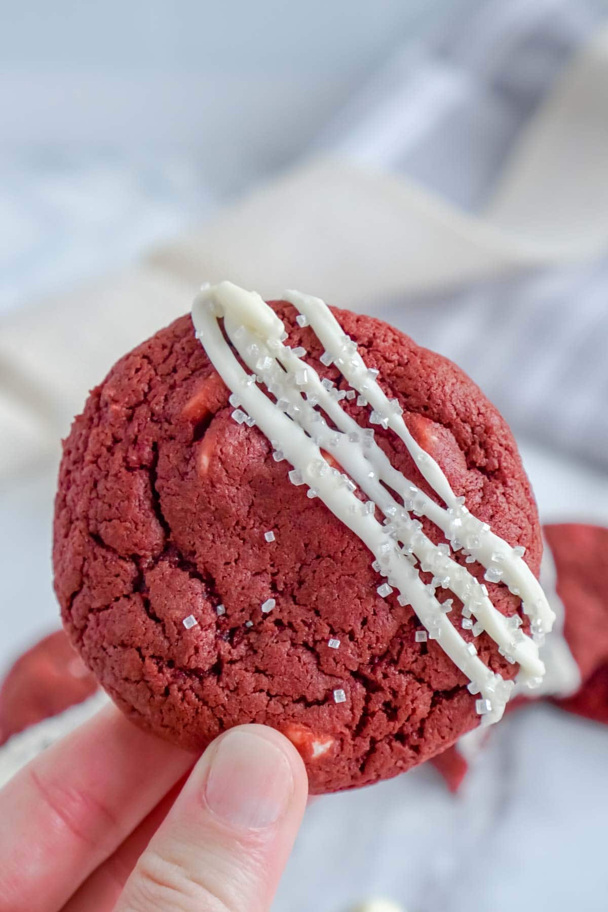 Woman's hand holding a red velvet cookie