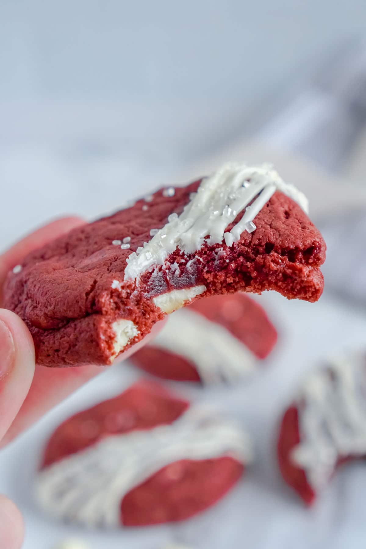 Woman's hand holding a red velvet cookie with frosting