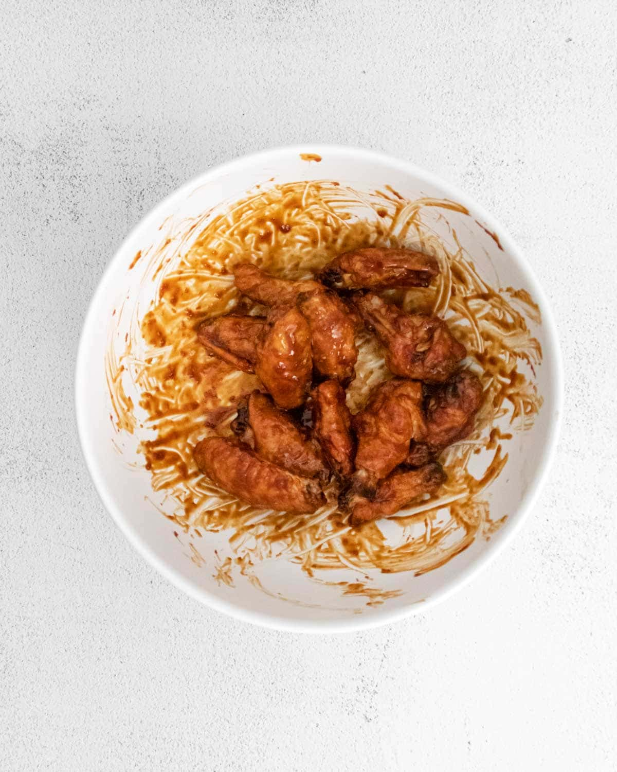 White bowl with sticky chicken wings