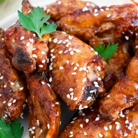 Close up image of sticky chicken wings with parsley