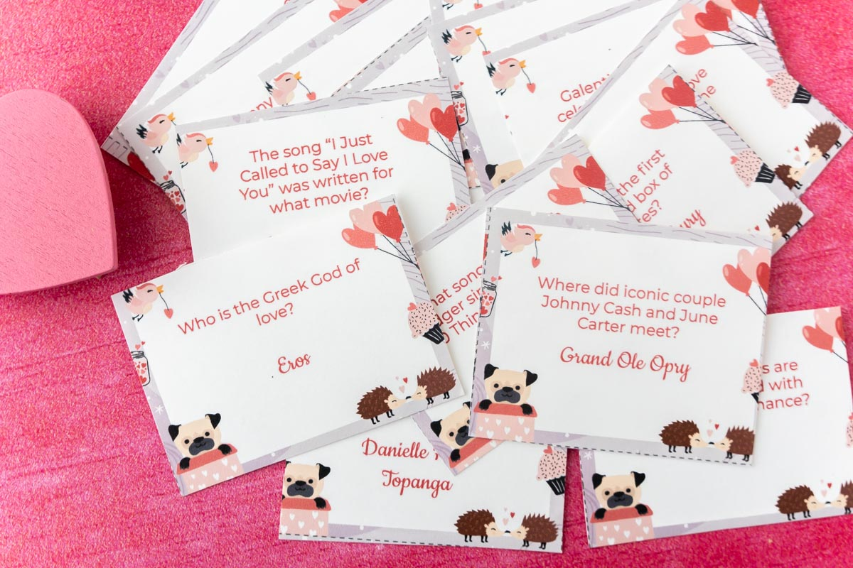 Pile of Valentines Day trivia cards on a pink background