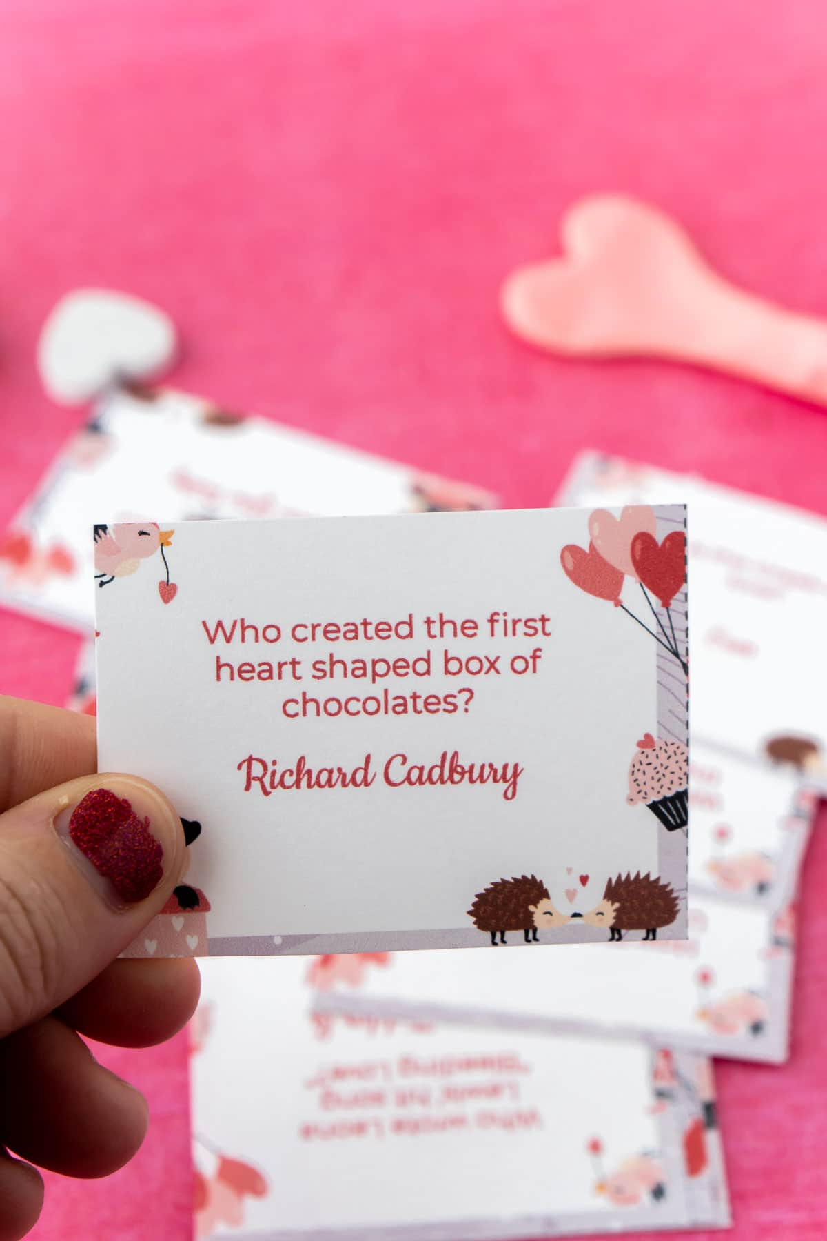 Woman's hand holding a Valentines trivia card