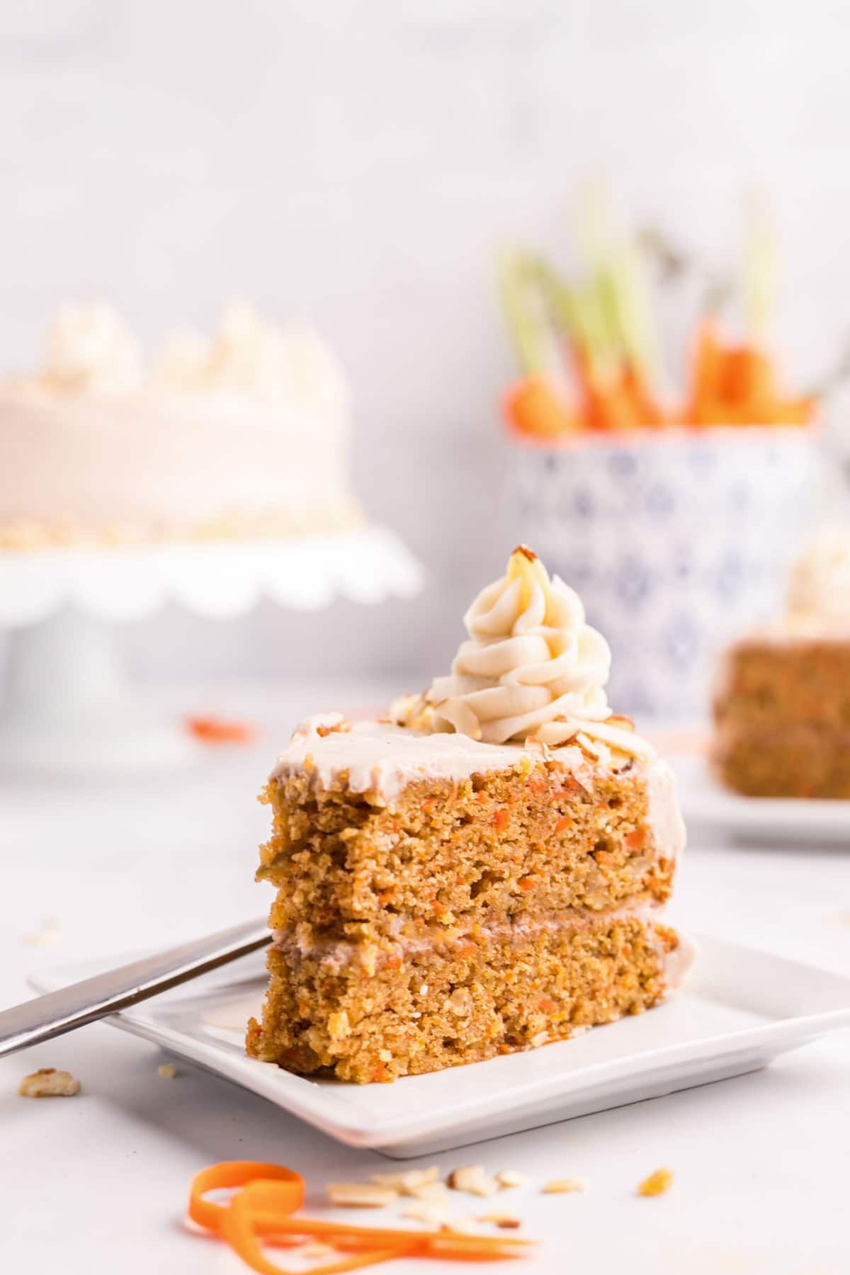 A slice of carrot cake with a dollop of cream cheese frosting on top