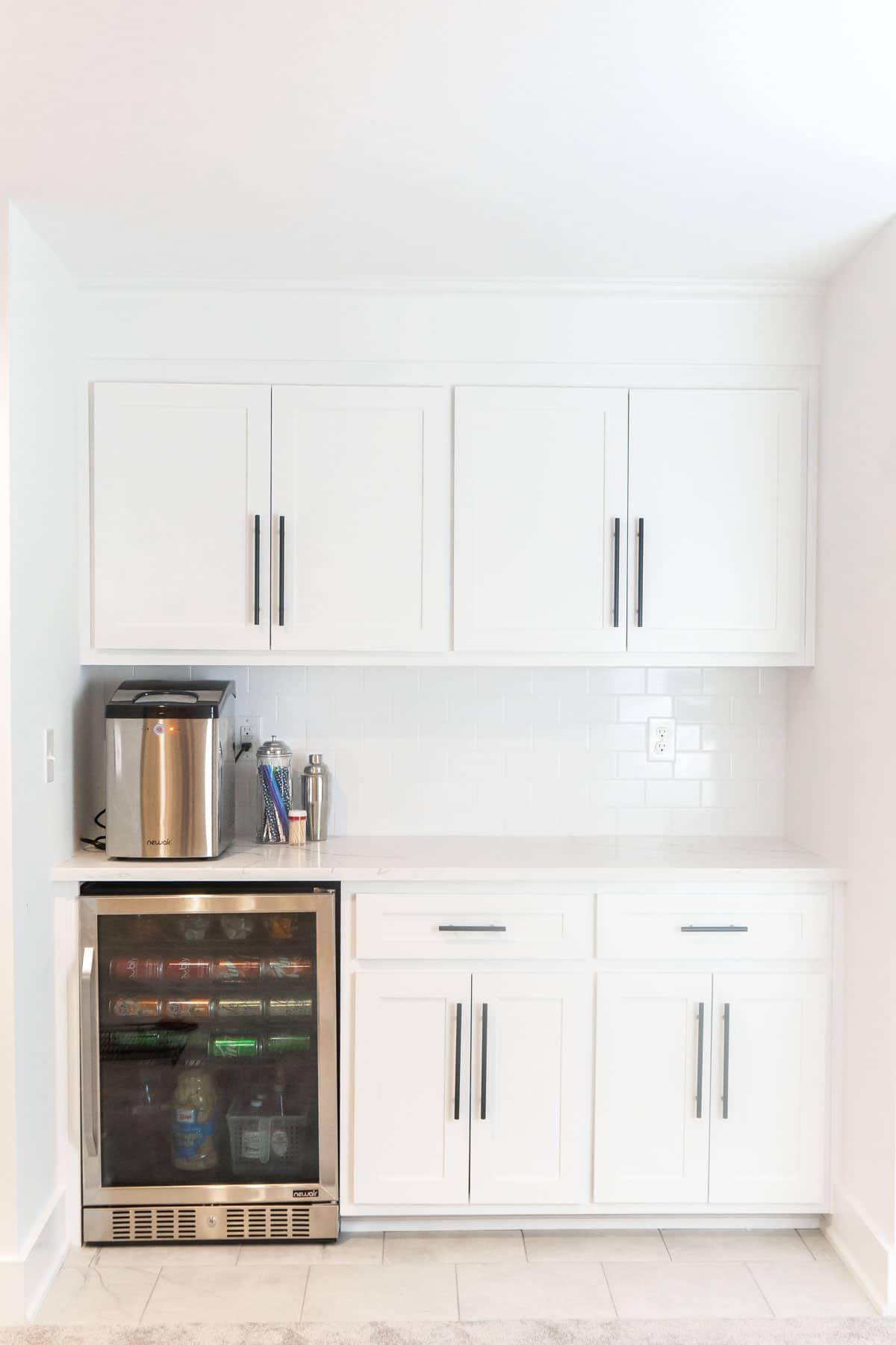 White basement dry bar with a mini fridge