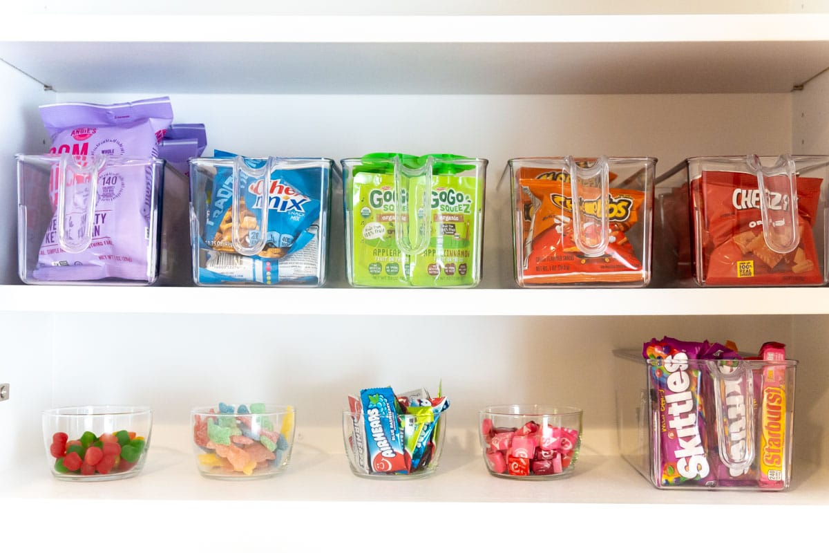 Snacks in clear plastic buckets in a cabinet