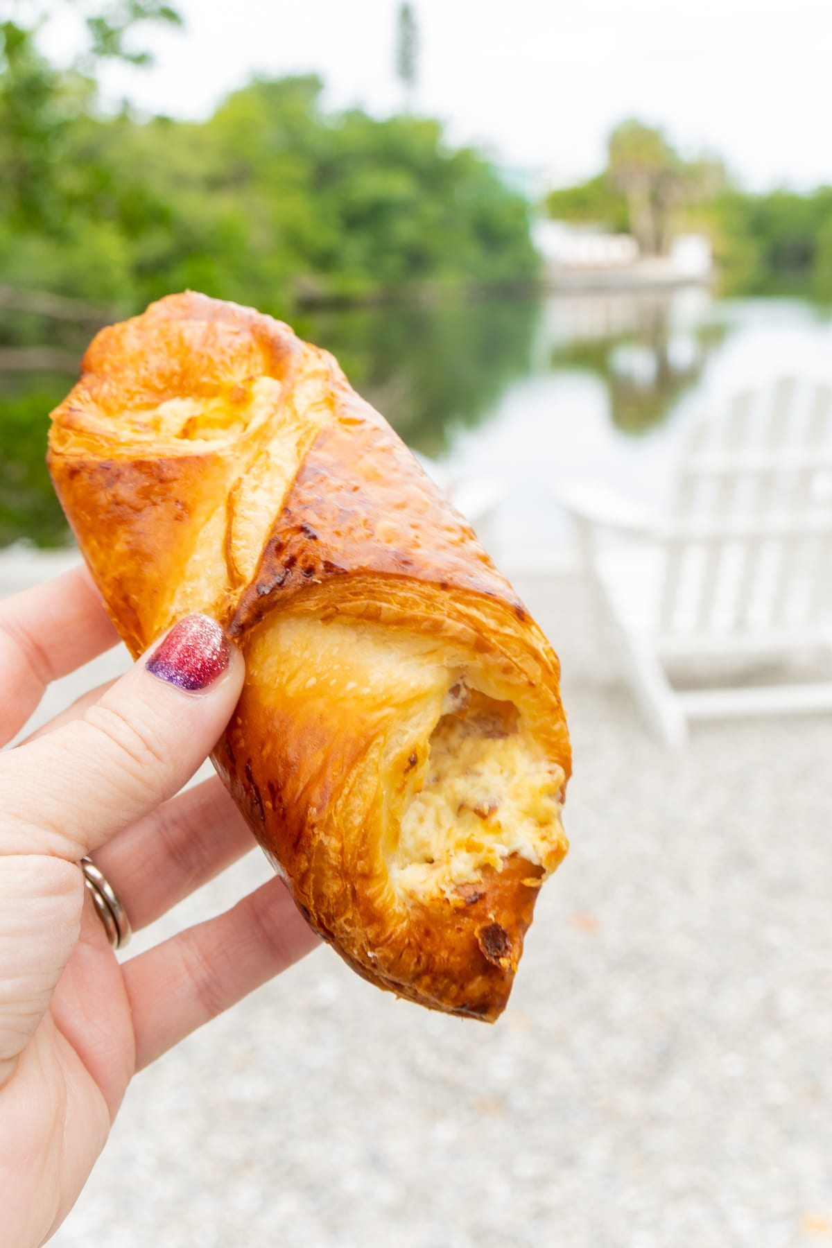Hand holding a ham and cheese croissant