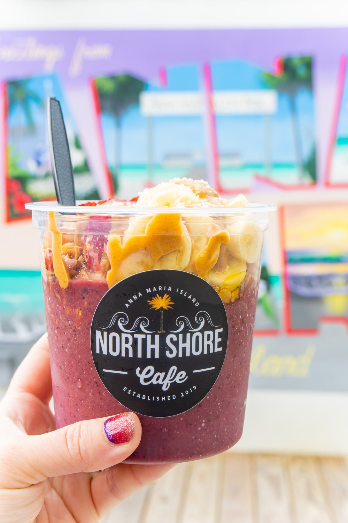 Acai bowl being held by a woman's hand