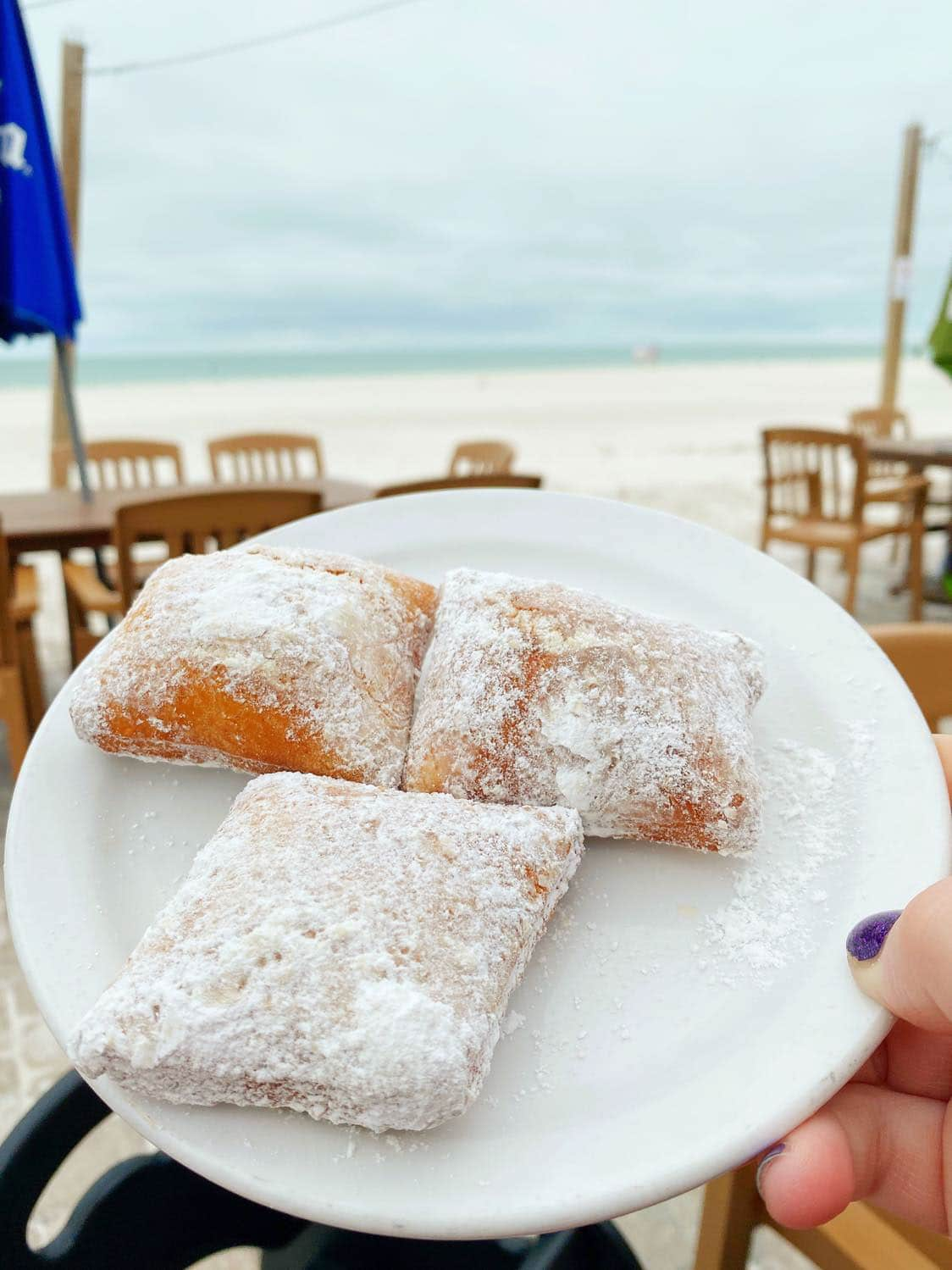 Plate of beignets with beach in the background