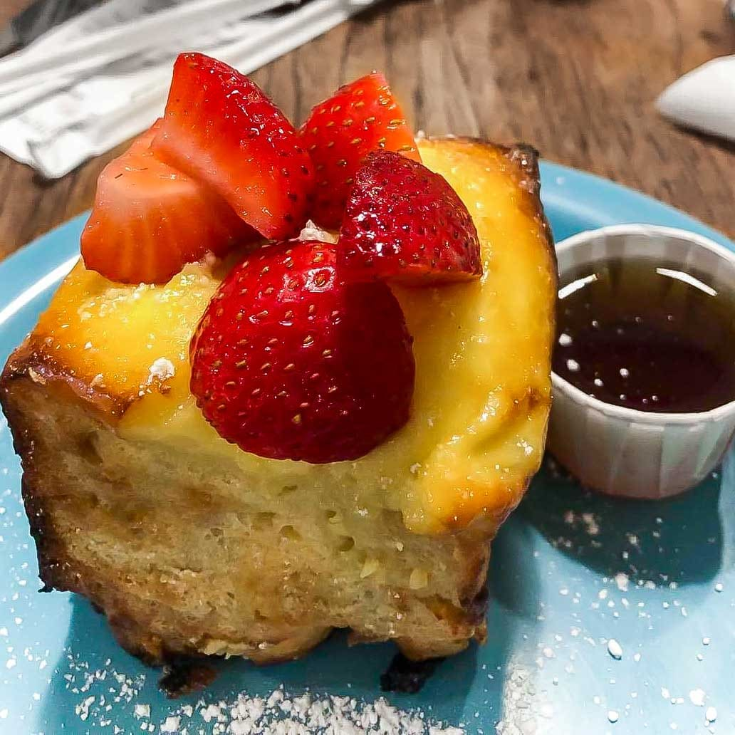 creme brulee French toast with strawberries on a blue plate