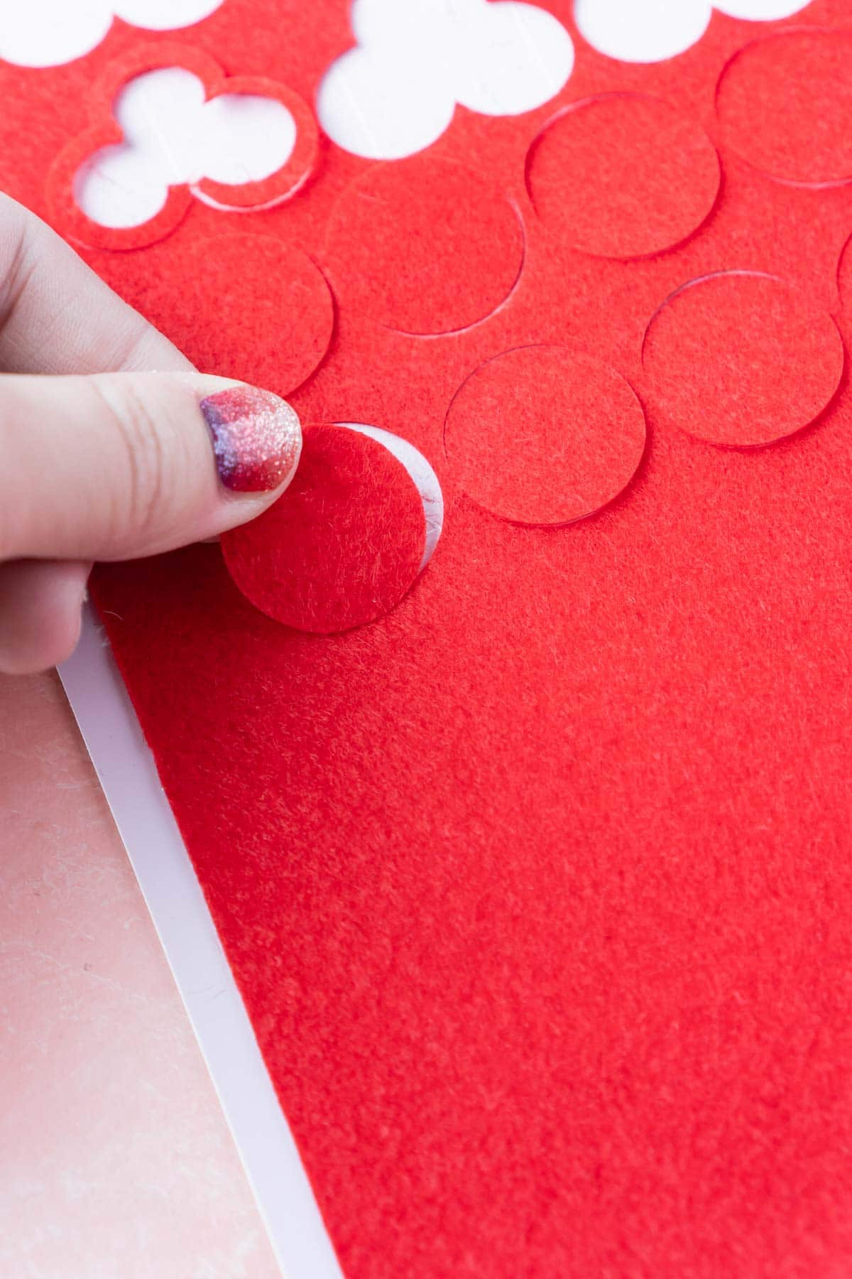 Hand pulling up a red felt circle from a red felt sheet