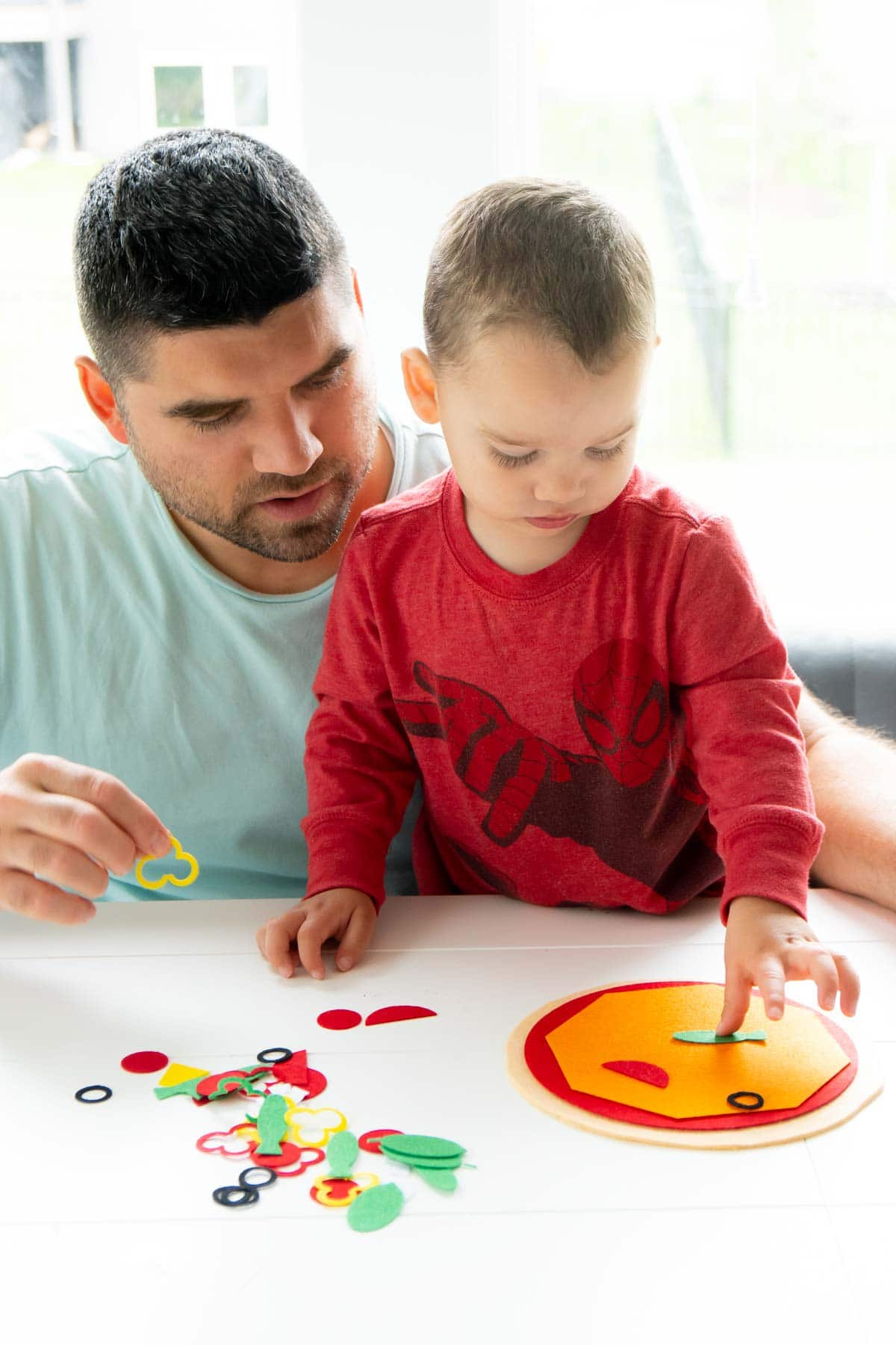 toddler playing with felt pizza set