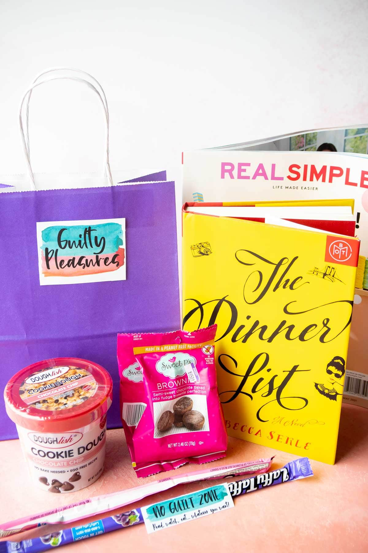purple gift bag with a book and magazine aroun