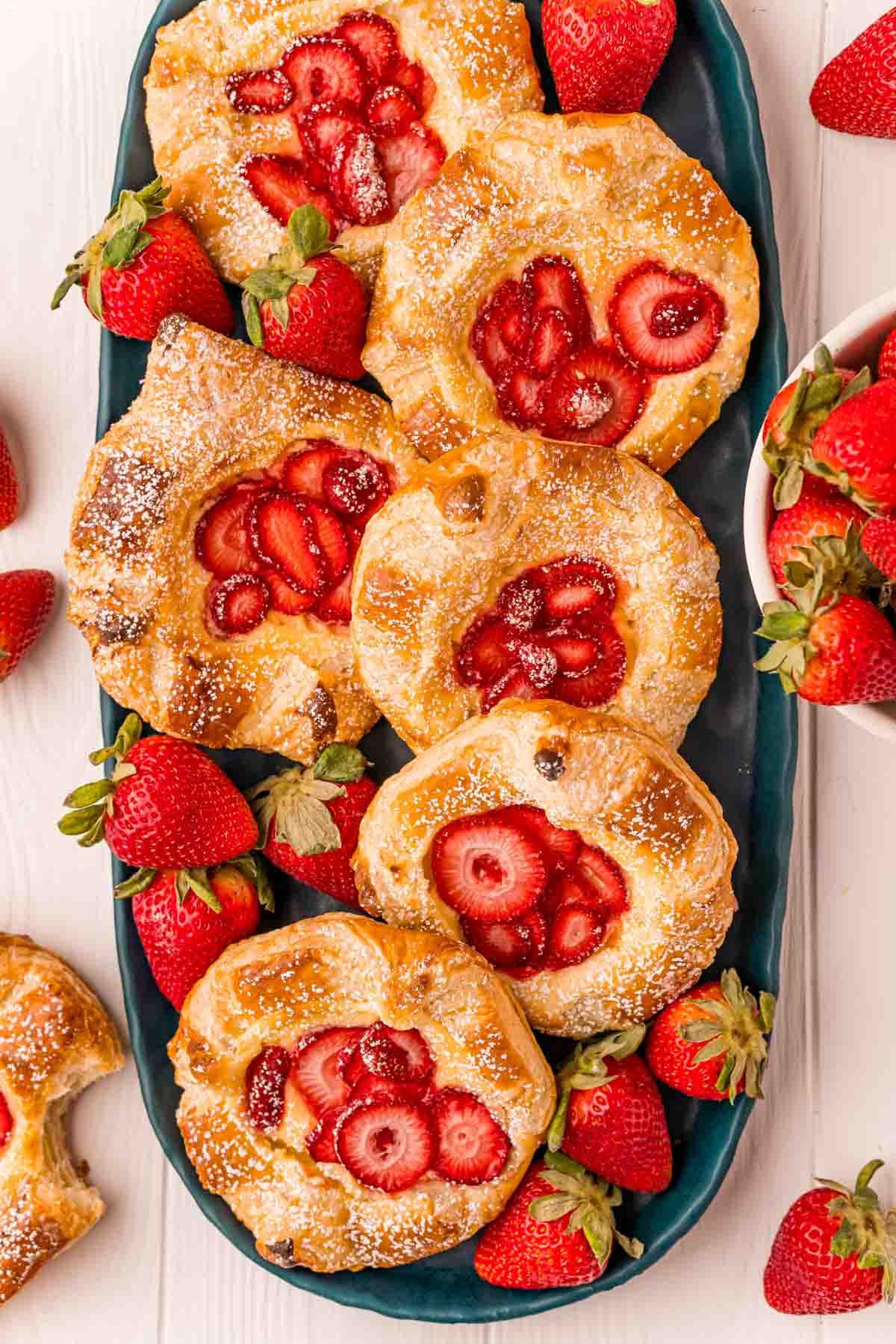 plate full of strawberry danishes with strawberries around
