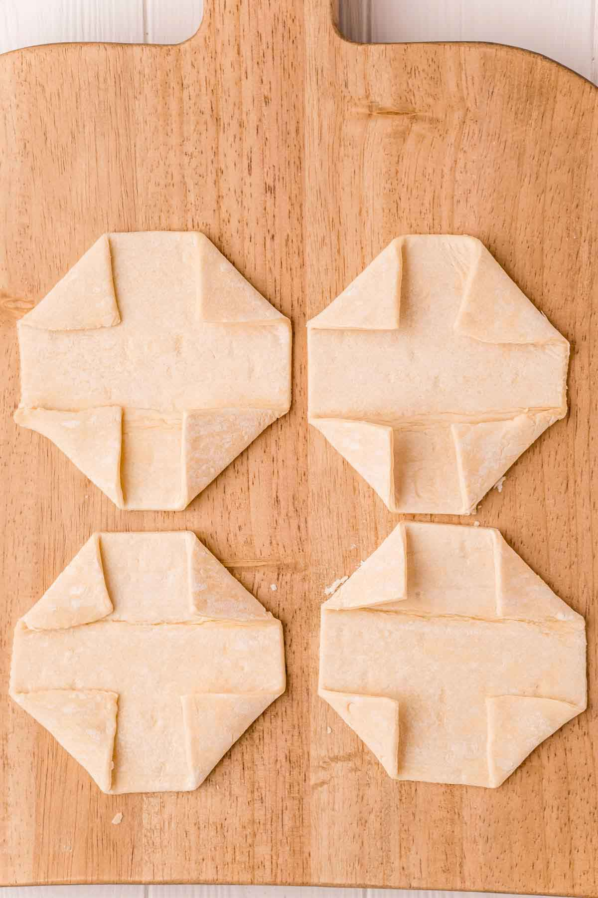 Four puff pastries on a cutting board