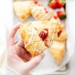 strawberry scone drizzled with vanilla frosting in someone's hand