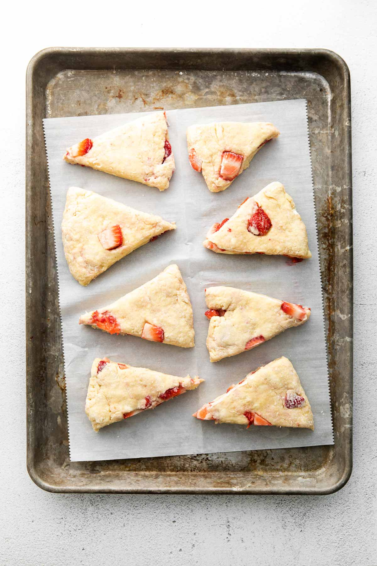 unbaked strawberry scones on a piece of parchment paper