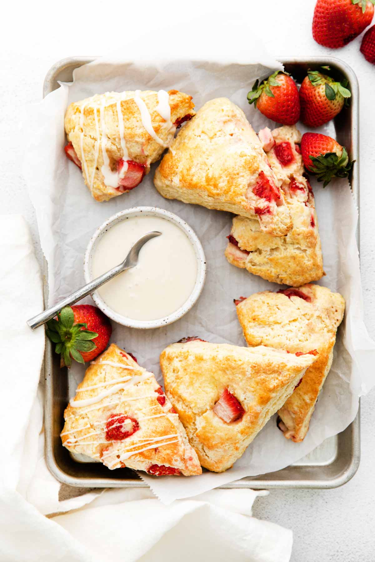 plate full of strawberry scones with a bowl of vanilla glaze