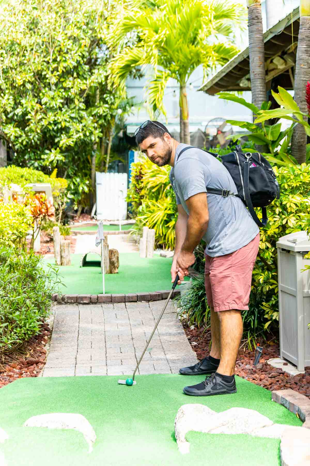 Man playing miniature golf