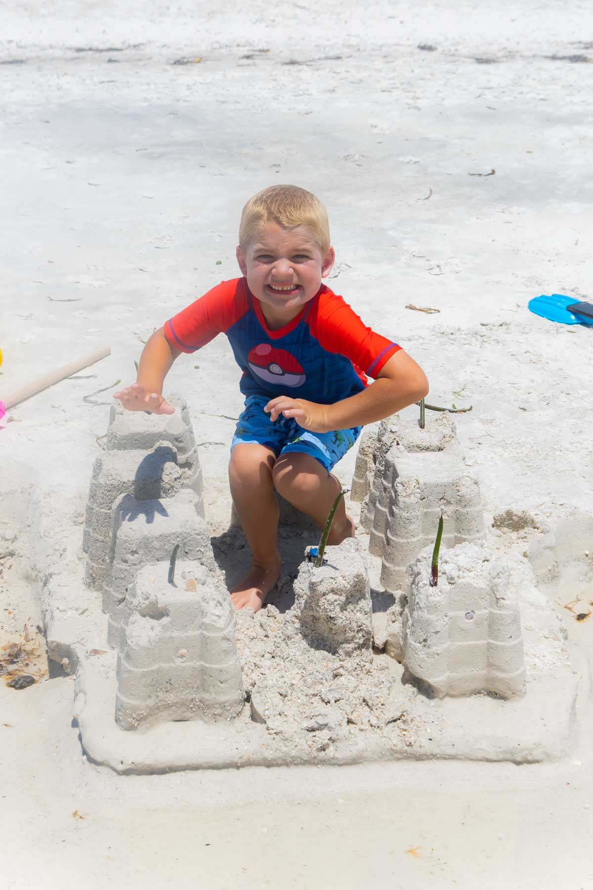 boy with a sand castle on the beach