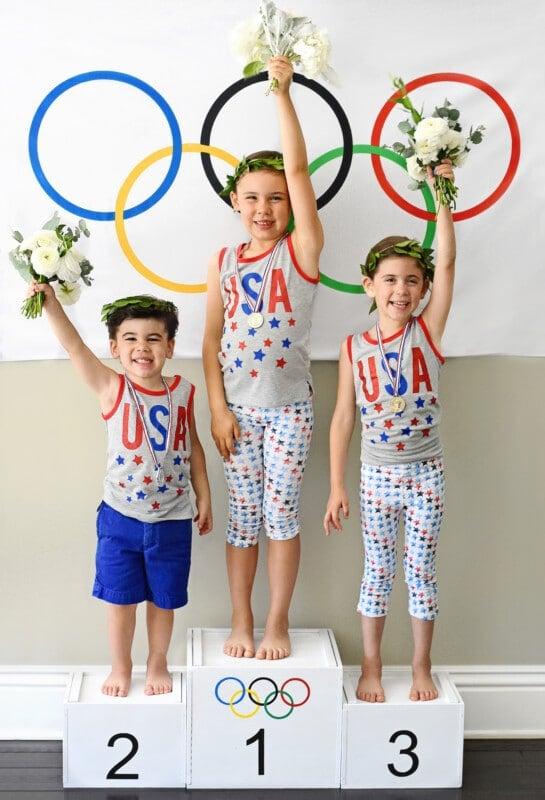 Three boys standing on a white podium