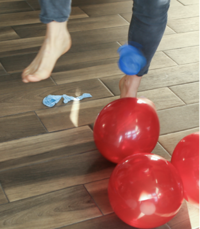 foot trying to pop red balloons