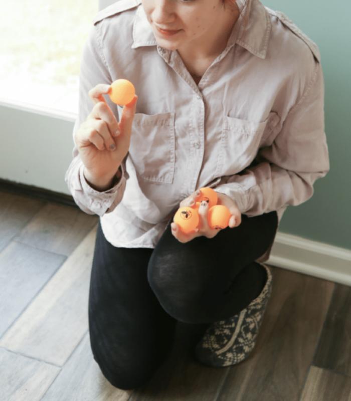 girl holding orange ping pong balls