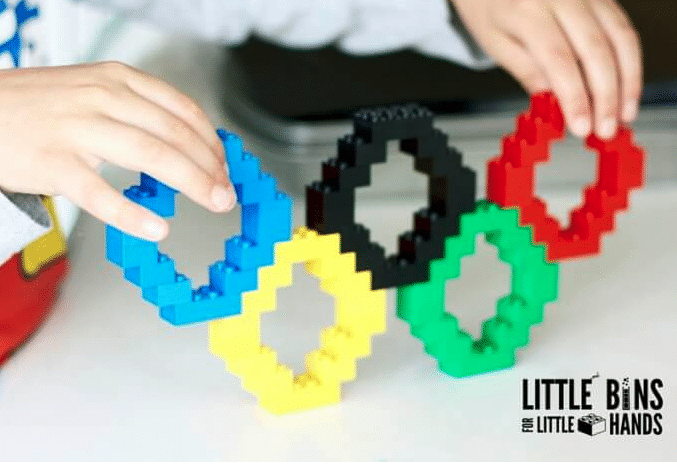 Hand holding Olympics rings made out of Legos