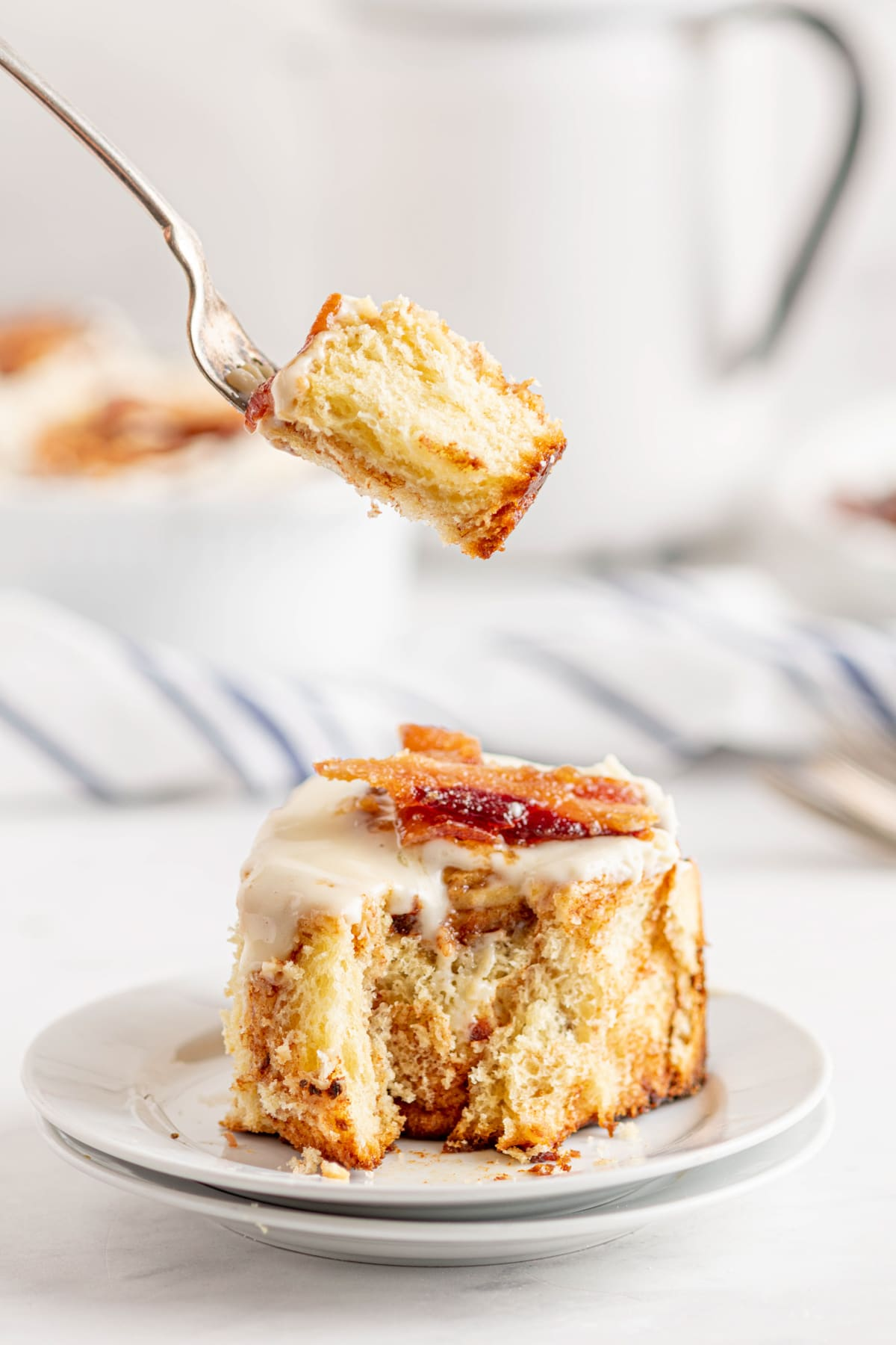 single bacon cinnamon roll with a bite out of it