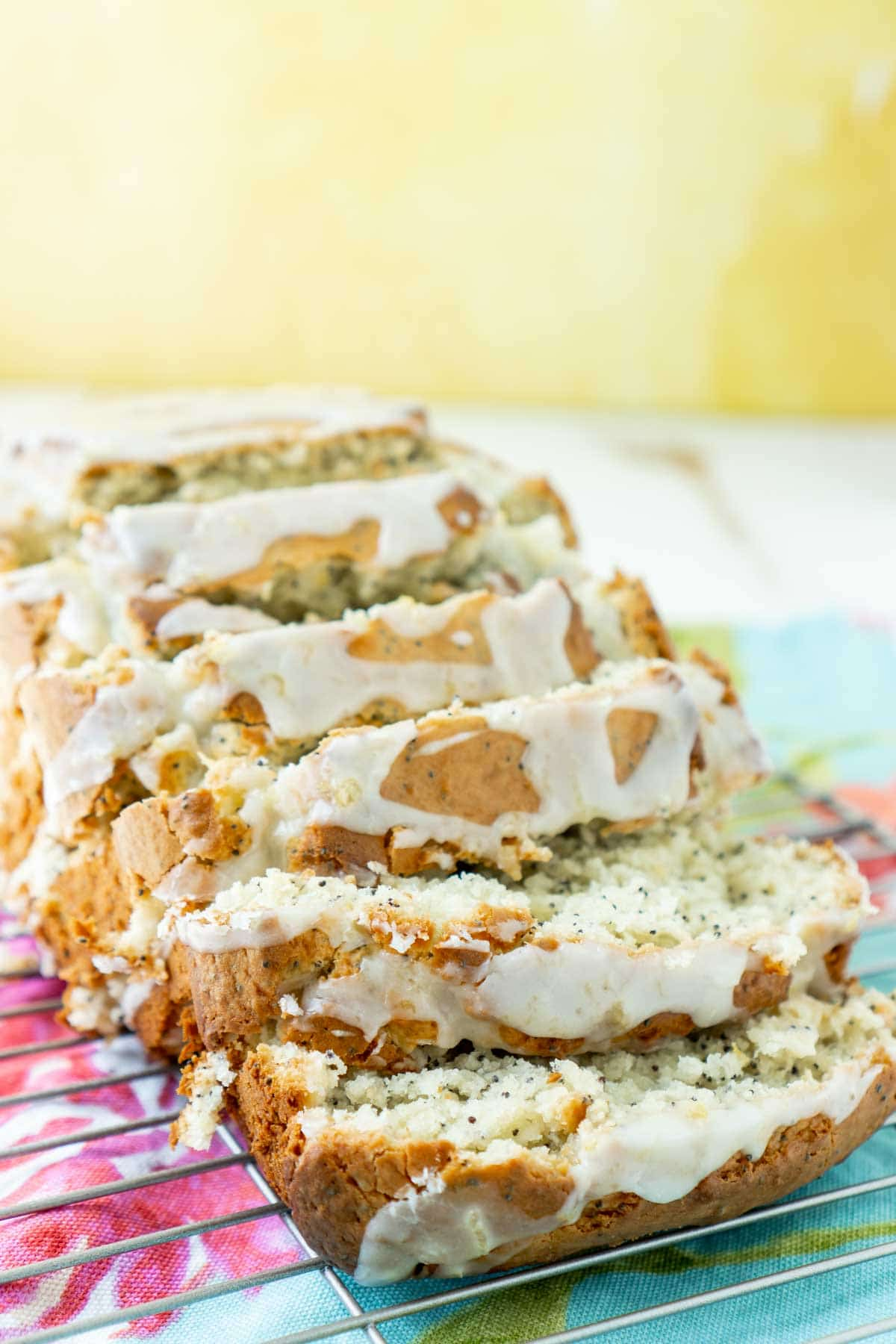 sliced lemon poppy seed bread with a yellow background
