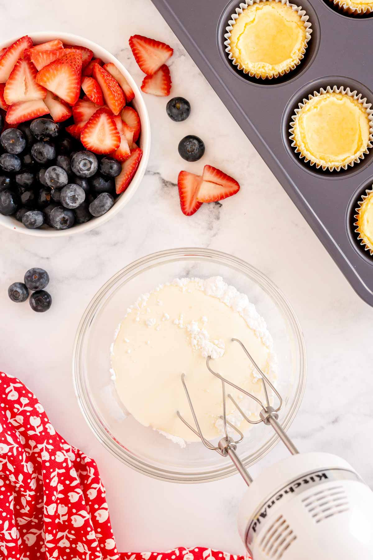 hand mixer in a bowl with cheesecake topping