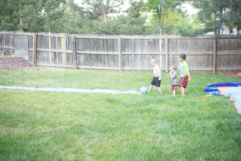 Kids standing at a slip and slide