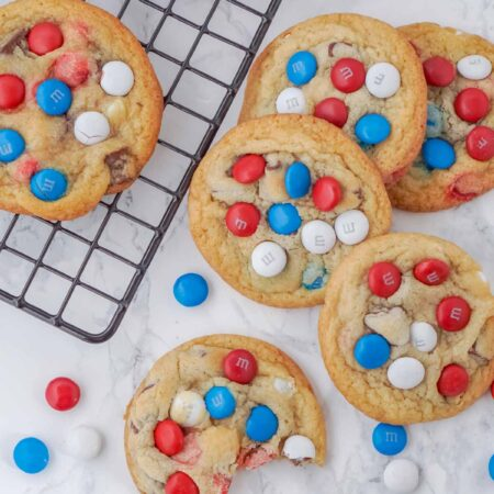chocolate chip M&M cookies on and next to a wire cooling rack
